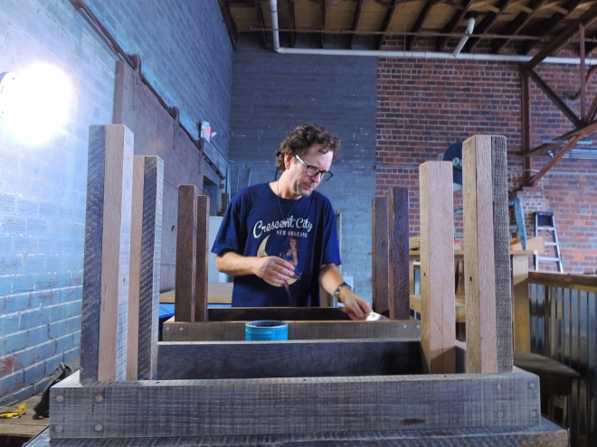 Eddie applies a custom finish to a reclaimed wood table at the Eco Relics wood shop   Come visit us today!