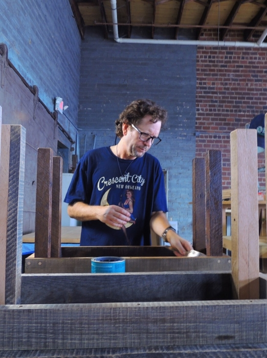 Eddie applies a custom finish to a reclaimed wood table at the Eco Relics wood shop | Come visit us today!