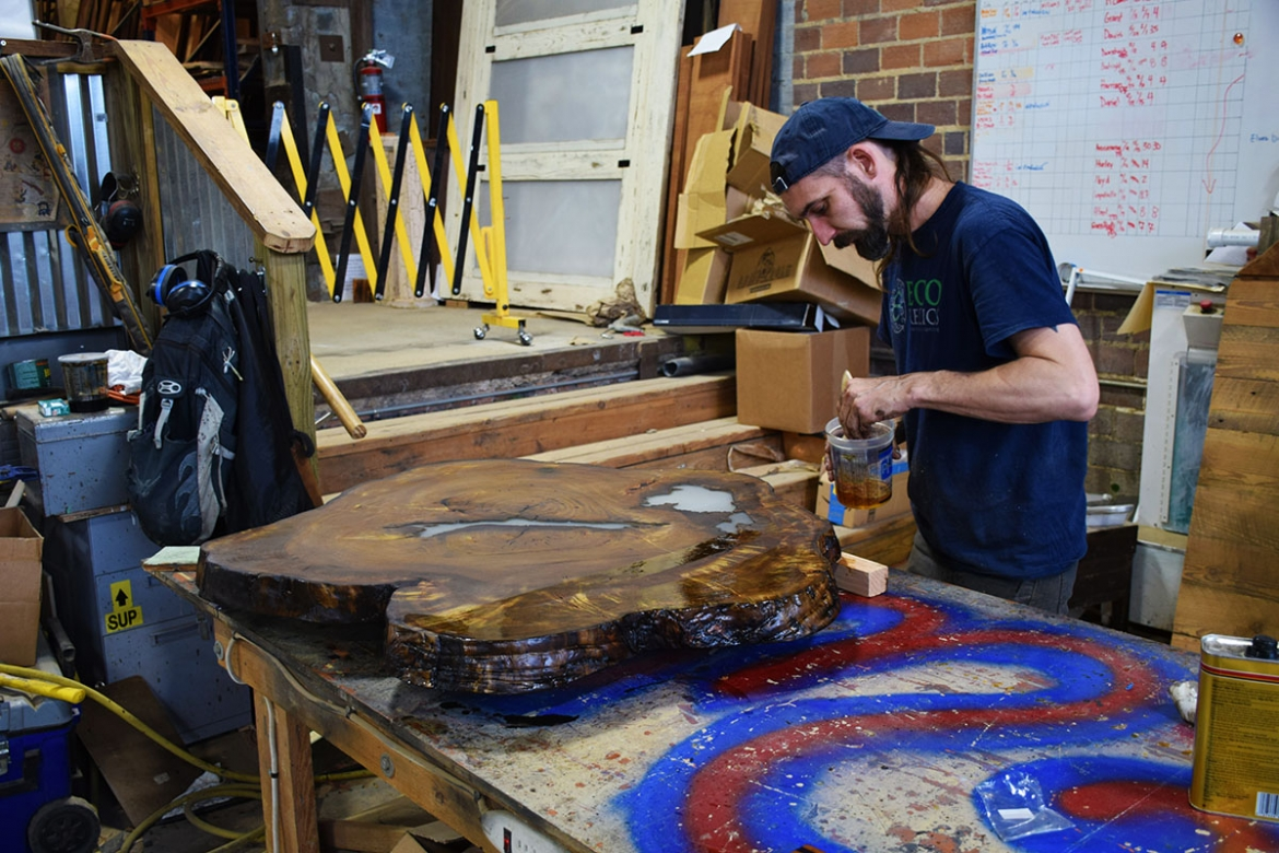 After stain has dried, Billy now applies a glossy finish coat.