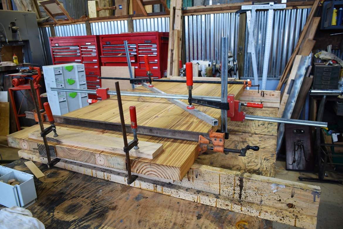 Authentic reclaimed heart pine being assembled for Custom Farm Table top.