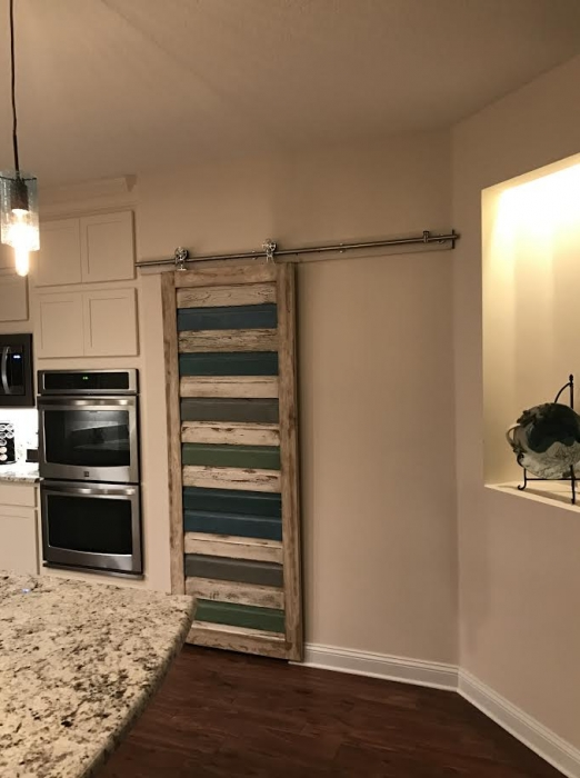 Beautifully hung custom barn door covering the pantry opening.