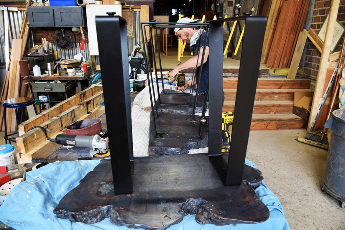 Custom made angular shaped metal legs being attached to live edge cookie slabs.