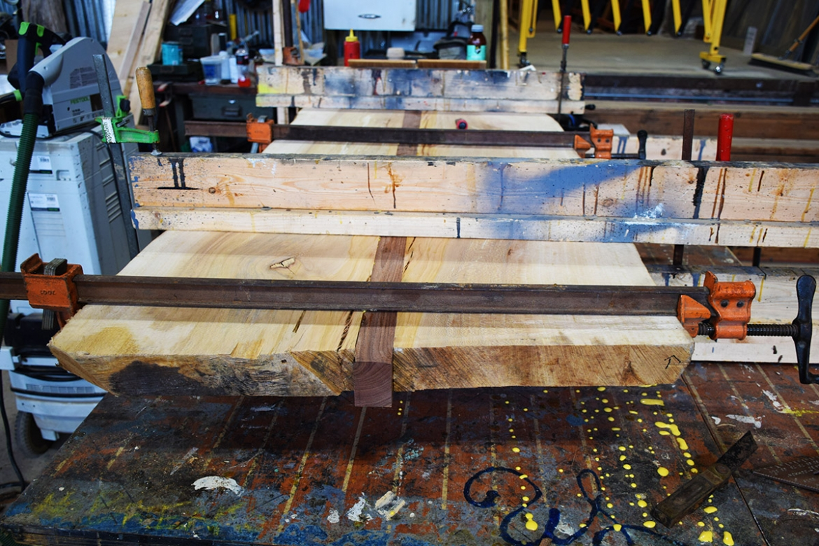 Sycamore slab cut, fitted with Black Walnut center strip, glued and clamped.