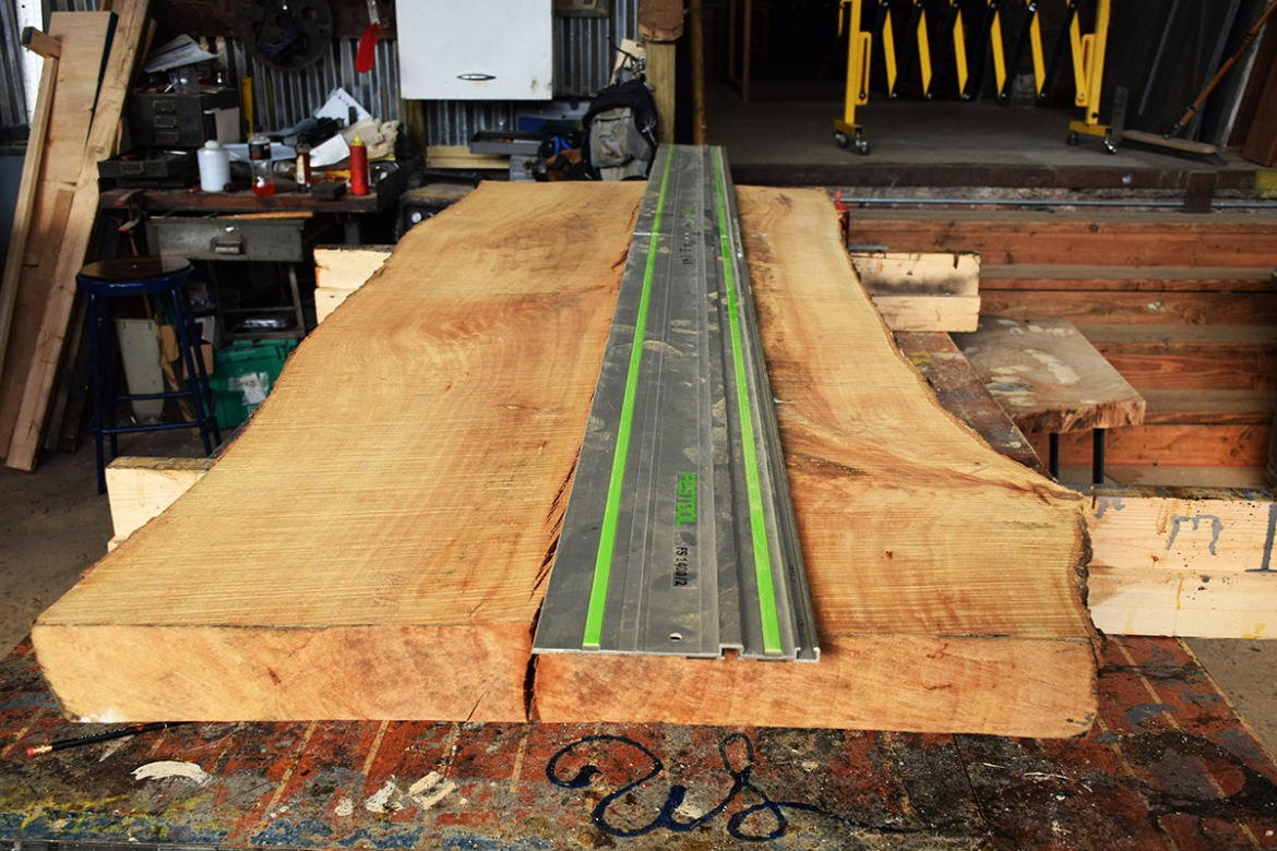Sycamore slab getting marked to be cut into two pieces.