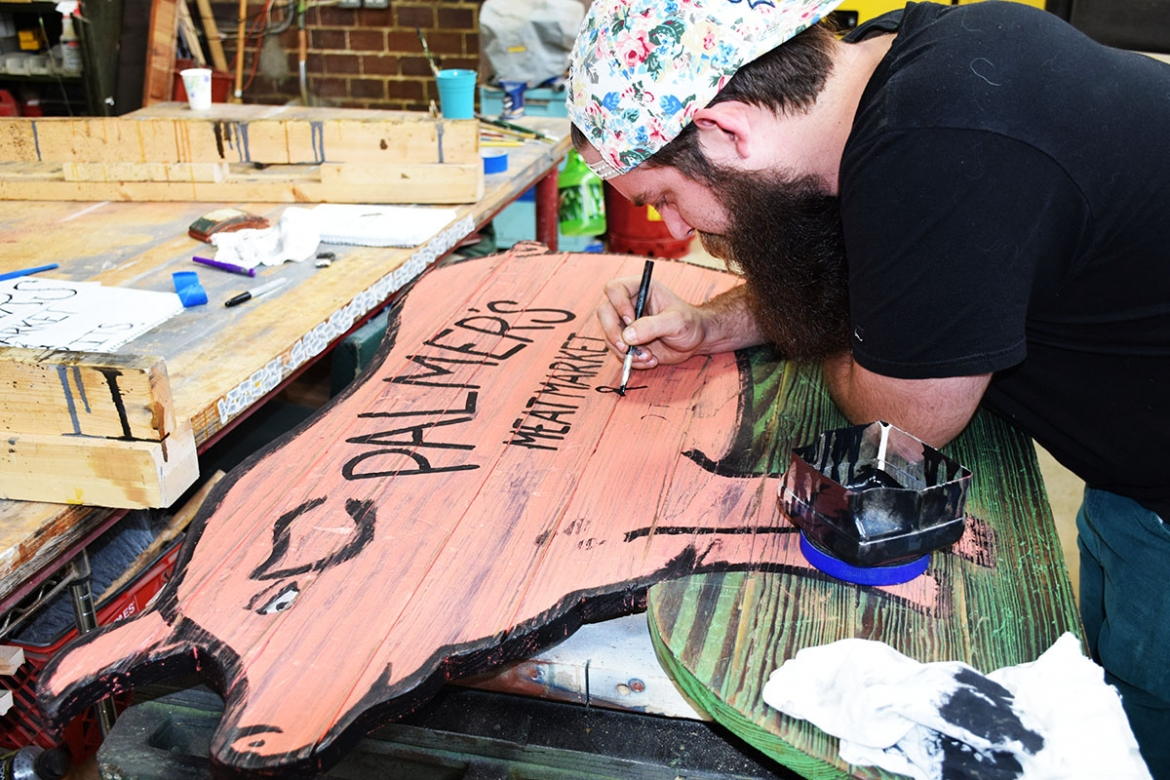 Parker begins painting the letters on the sign.