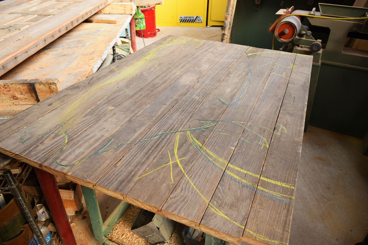 After joining the salvaged boards, Parker traces out the shape of the sign.